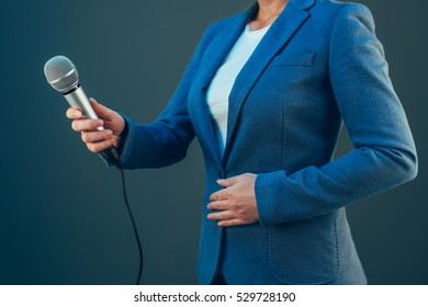 Elegant female journalist conducting business interview or press conference, hand with microphone