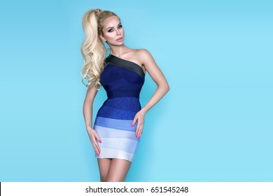 Elegant female model in a  mini dress standing on a blue background and sensually poses