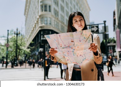 elegant female tourist travel alone in spring holidays to san francisco holding paper map searching direction of famous attraction. white flatiron building in background under sunlight in summer.