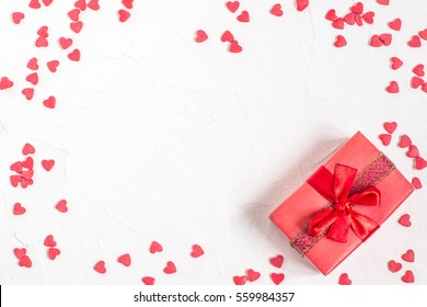 Elegant festive background with sugar decorations in the form of heart and gift box with bow on white textured surface with space for text. The mood of tenderness and love. Symbols of Valentines Day