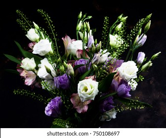Elegant Flowers Bouquet with White and Purple Lisianthus, Alstroemeria and Decorative Green Stems closeup on Dark Grunge background