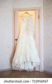 Elegant flowing wedding dress hanging from door