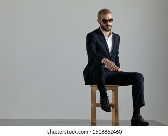elegant formal business man wearing a navy suit and sunglasses sitting with one leg resting on a chair and one hand resting on the leg while looking away pensive on gray studio background