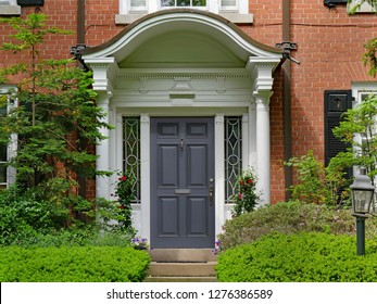 elegant front door with portico and shrubs