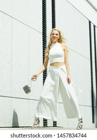Elegant funny, playful fashionable woman presenting trendy urban outfit. White crop top and trousers culottes. Female having fun.