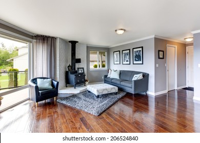 Elegant furnished corner in luxury house living room. View of antique stove with white brick background, coach and chair.