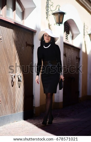 757ba281446 Elegant girl in black in the style of coco chanel walking in the city