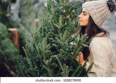 Elegant girl buys a Christmas tree. Woman in a white knited sweater. Beautiful lady with dark hair.