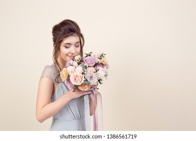 Elegant girl with a haircut in a soft blue dress and make-up is holding a bouquet of a stylish bouquet of flowers.