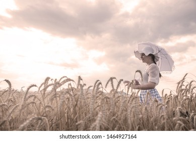 Elegant girl with a parasol and a hat set in a field of wheat