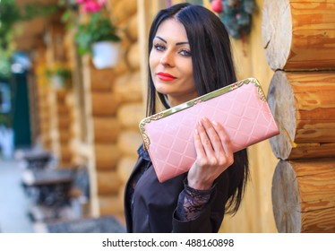 Elegant girl with pink handbag clutch in hand . Stylish outfit with accessories watch