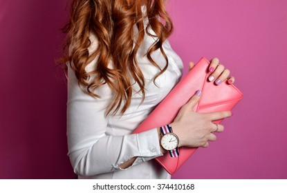 Elegant girl with pink leather handbag clutch in hand . Stylish outfit with accessories watch