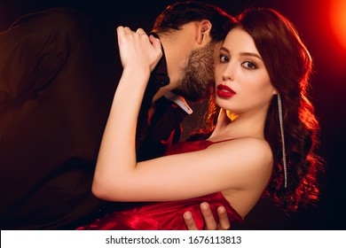 Elegant girl in red dress looking at camera while hugging boyfriend on black background with lighting