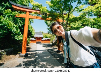elegant girl traveler standing in front of the Torii and taking selfie in Japan. young tourist visiting Japanese temple taking self portrait photo in the trip. famous places to visit in kyoto.