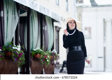 Elegant girl in a white hat near the cafe