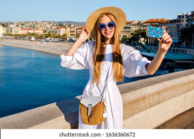 Elegant glamour magnificent woman wearing luxury white dress and straw accessories making selfie at beach front in French Riviera, traveling goals, bright sunny colors, blue ocean.