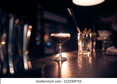 elegant glass with espresso martini cocktail on blue background; luxury drink on the bar and with decoration;