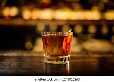 Elegant glass filled with strong cocktail with whiskey on the bar counter in background of the lights