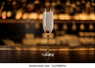 Elegant glass of fresh French 75 cocktail with cherry on the bar counter against the golden lights