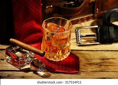 elegant glass of whiskey on the rocks and cigar with clothing accessories