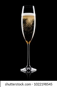 Elegant glass of yellow champagne with bubbles on black background with reflection