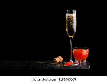 Elegant glass of yellow champagne with red caviar on golden spoon and glass container of caviar on marble board on black background