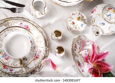 Elegant gold design white porcelain tableware with hand painted gold elements. Table arrangement of luxury porcelain set for tea or coffee