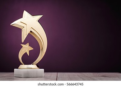 Elegant gold winners trophy with shooting stars to be awarded for the first place in a competition or championship over a dark purple background with copy space
