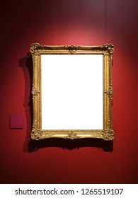 Elegant golden blank picture frame of classic style on the red wall