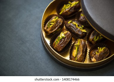 An elegant golden color gift box filled with premium quality pistachio-stuffed dates. Pack of gourmet Arabic dates with partially open lid on clean background.