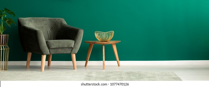 Elegant, golden fruit bowl on a wooden side table and a comfortable armchair in a teal green living room interior with copy space