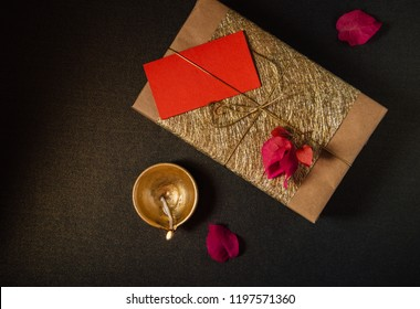 An elegant golden Indian festive gift pack and traditional terracotta lamp in dark background. View from top.