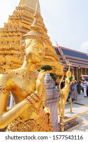 Elegant golden Kinnari statue at Grand Palace, Bangkok, Thailand, A group of tourists appreciating the Grand Palace blurred in the backgrounds. The Grand Palace is open to the public.