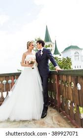 Elegant gorgeous happy  bride and groom standing on the balcony