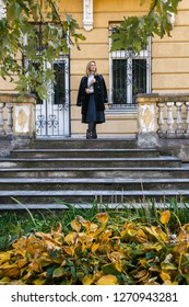 Elegant gorgeous woman wearing in black coat posing on staircase of old house