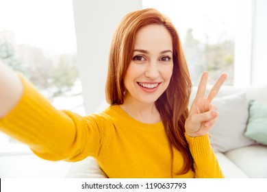 Elegant, graceful, charming, cheerful, fancy lady with straight hair take selfie on front camera of smartphone, sit on cozy soft white couch in yellow sweater make v-sign and beaming smile
