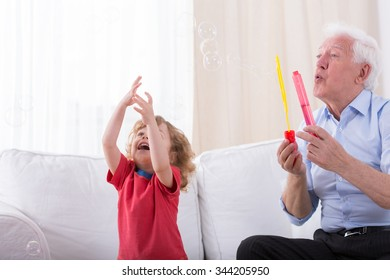 Elegant grandfather letting soap bubbles with grandson