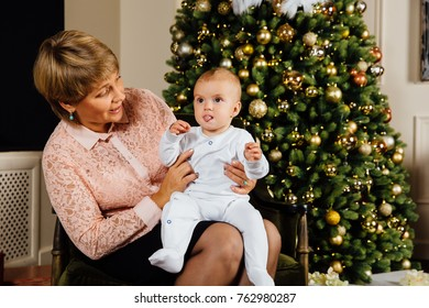 Elegant grandmother with a child in her arms on the background of a Christmas tree. Fashionable New Year decoration of a tree. Newborn in white sliders. Business grandmother.