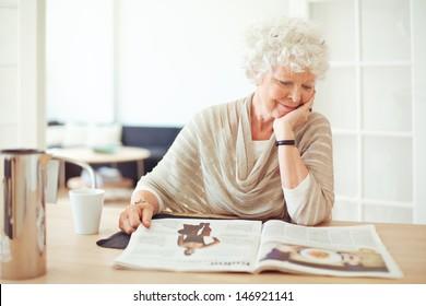 Elegant grandmother sitting at home reading a magazine