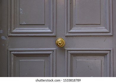 Elegant gray color painted wooden door surface with relief frames and round vintage knob in center. Details of Paris door of old building in France. Simplicity of classic architecture.