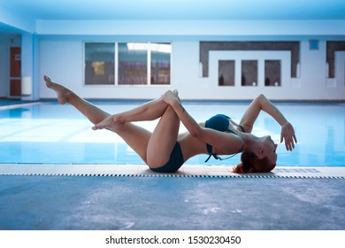 Elegant green swimsuit model woman doing yoga by the pool