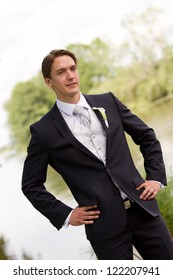 Elegant groom with self confident pose in front of a lake