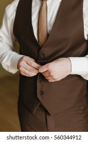 Elegant groom wearing white shirt and brown vest and tie. Groom's hands on suit. Close up photo. Groom's morning preparation details