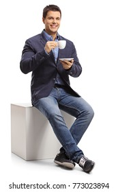 Elegant guy sitting on a cube and holding a cup isolated on white background
