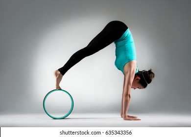 elegant gymnastics teacher inverted hands support body on floor and legs on pilates ring with stretch body develop softness in gray wall background studio.