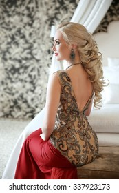 Elegant hairstyle. Beautiful blond woman in fashion red dress sitting on modern sofa at luxurious interior apartment with furniture.