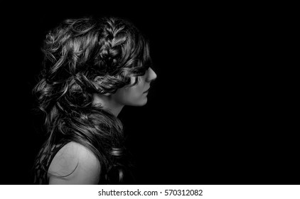 Elegant hairstyle with braids on beautiful woman. Studio photography. Black and white