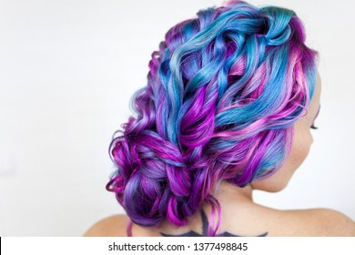Elegant hairstyle of curls on long colored hair, styling. Bright color coloring, concept. Young woman with bright bold hair color