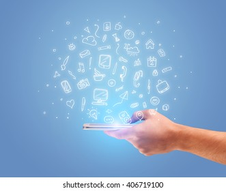 An elegant hand holding mobile phone with drawn social media icons in front of an empty clear blue background concept