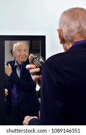 Elegant handsome grey haired senior man dressed in business casual using perfume on luxury black background looking at mirror. Health care, beauty and lifestyle concept.